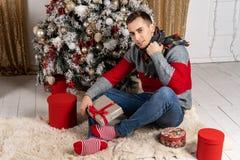 Stilig ung man med en halsduk som sitter med gåvor på plädet nära julgranen arkivbilder