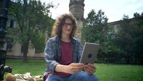 Stilig ung man med lockigt hår i exponeringsglas som har video pratstund till och med minnestavlan och säger farvälet som ler, ga arkivfilmer