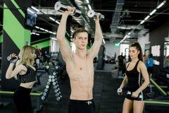 Stilig ung man med muskulöst naket torsoanseende i idrottshallen och drevbiceps med hantlar samman med två royaltyfri bild