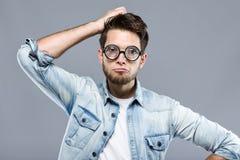 Stilig ung man med roliga exponeringsglas som skojar och gör den roliga framsidan över grå bakgrund Royaltyfri Bild