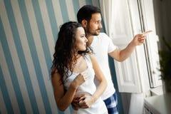 Stilig ung man och härlig kvinna som ser till och med fönster royaltyfri foto
