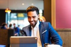 Stilig ung man på dräkt genom att använda bärbara datorn arkivfoton