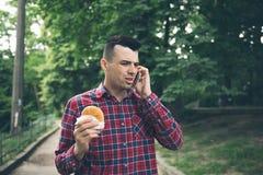 Stilig ung man som äter smörgåsautdoor Han rymmer en telefon Arkivfoto