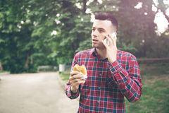 Stilig ung man som äter smörgåsautdoor Han rymmer en telefon Royaltyfri Foto