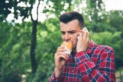 Stilig ung man som äter smörgåsautdoor Han rymmer en telefon Royaltyfri Bild