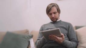Stilig ung man som använder hans digitala minnestavla med leende, medan ligga ner på soffan hemma Spendera stor tid på arkivfilmer
