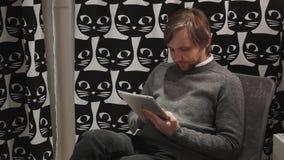 Stilig ung man som använder hans digitala minnestavla med leende, medan ligga ner på soffan hemma Spendera stor tid på lager videofilmer
