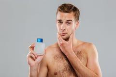 Stilig ung man som applicerar lotion efter rakning på framsida Arkivfoton