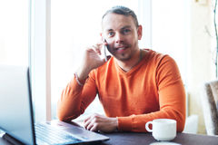 Stilig ung man som arbetar med anteckningsboken och att tala på telefonen, le som ser kameran, medan tycka om kaffe i kafé Arkivbild