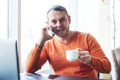 Stilig ung man som arbetar med anteckningsboken och att tala på telefonen, le som ser kameran, medan tycka om kaffe i kafé Arkivfoto