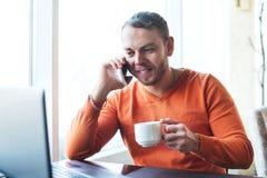 Stilig ung man som arbetar med anteckningsboken och att tala på telefonen som ler, medan tycka om kaffe i kafé Royaltyfri Bild