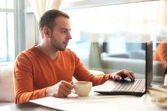 Stilig ung man som arbetar på anteckningsboken som tänker, medan tycka om kaffe i kafé Arkivfoto