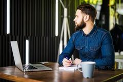 Stilig ung man som arbetar på bärbara datorn och ler, medan tycka om kaffe i kafé Arkivbild