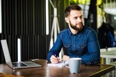Stilig ung man som arbetar på bärbara datorn och ler, medan tycka om kaffe i kafé Arkivfoto