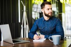 Stilig ung man som arbetar på bärbara datorn och ler, medan tycka om kaffe i kafé Fotografering för Bildbyråer
