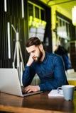 Stilig ung man som arbetar på bärbara datorn och ler, medan tycka om kaffe i kafé Royaltyfria Foton