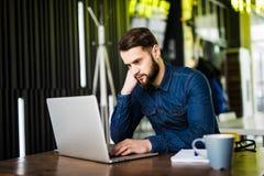 Stilig ung man som arbetar på bärbara datorn och ler, medan tycka om kaffe i kafé Royaltyfri Foto