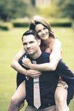 Stilig ung man som bär hans fiance på hans baksida Royaltyfri Fotografi
