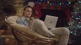 Stilig ung man som direktanslutet shoppar, genom att använda bärbara datorn och kreditkorten i Xmas-natt stock video