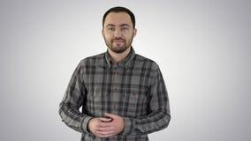 Stilig ung man som g?r och ser till kameran och pekar till sidovisningen n?got p? lutningbakgrund stock video