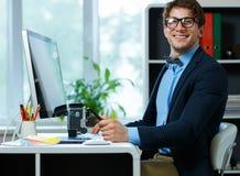 Stilig ung man som hemifrån arbetar kontoret Arkivbild