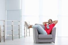 Stilig ung man som inomhus vilar i fåtölj royaltyfri foto