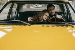 stilig ung man som kör bilen och omfamnar den härliga eftertänksamma flickvännen royaltyfria foton