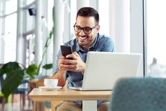 Stilig ung man som ler och ser hans telefon medan på lunchavbrott arkivfoton