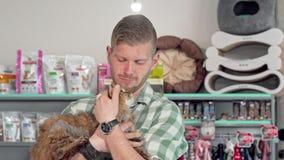 Stilig ung man som ler till kameran som rymmer den gulliga katten i hans armar stock video