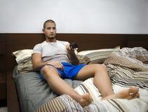 Stilig ung man som lägger på hans hållande ögonen på TV för säng Royaltyfria Foton