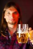Stilig ung man som rymmer en råna av öl arkivfoto