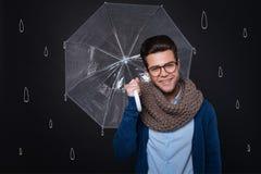 Stilig ung man som rymmer ett paraply fotografering för bildbyråer