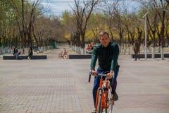 Stilig ung man som sitter på cykeln och smilling i staden arkivbild