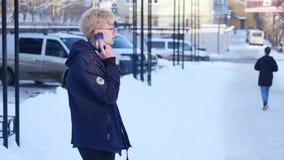Stilig ung man som talar på en mobil på gatan av storstaden lager videofilmer