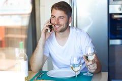 Stilig ung man som talar på smartphonen, medan dricka vitt vin i köket hemma arkivfoton