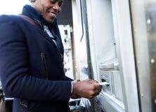 Stilig ung man som tar kassa från ATM med kreditkorten arkivfoto