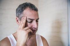 Stilig ung man som trycker på hans huvud med en hand som känner den starka huvudvärken, slut upp fotoet Fotografering för Bildbyråer
