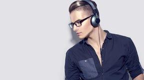 Stilig ung man som tycker om musik på hörlurar Royaltyfri Bild