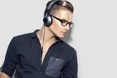 Stilig ung man som tycker om musik på hörlurar Fotografering för Bildbyråer