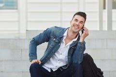 Stilig ung man som utanför ler på mobiltelefonappell Royaltyfri Foto