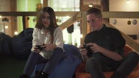 Stilig ung manlig arbetare med den kvinnliga kollegan som har roligt på avbrottet som spelar videospel med utmärkt lynne i modern arkivfilmer