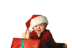Stilig ung pojke i jultomten röda hatt som rymmer en gåvaask Royaltyfria Foton