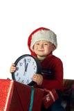 Stilig ung pojke i jultomten röda hatt som rymmer en gåvaask Royaltyfri Fotografi