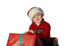 Stilig ung pojke i jultomten röda hatt som rymmer en gåvaask Arkivbilder