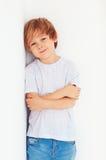 Stilig ung pojke, unge som poserar nära den vita väggen royaltyfria bilder