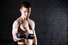 Stilig ung shirtless man med den muskulösa sexiga kroppen som gör övningar genom att använda hanteln mot en tegelstenvägg Arkivbilder