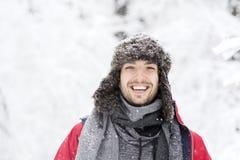 Stilig ung skratta man i forestsnowing dag för vinter Fotografering för Bildbyråer