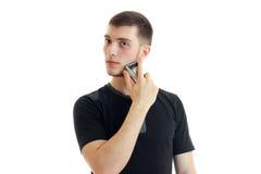 Stilig ung stark grabb i en svart t-skjorta och blickar in mot rakningar hans skäggnärbild Fotografering för Bildbyråer