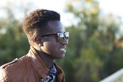 Stilig ung svart man i solglasögon och ett läderomslag på a Royaltyfri Bild