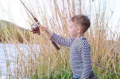 Stilig ung unge som rymmer hans metspö Fotografering för Bildbyråer